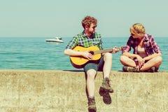 Jeune homme jouant la guitare à son amie extérieure Photographie stock