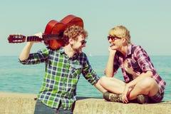 Jeune homme jouant la guitare à son amie extérieure Image stock