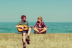 Jeune homme jouant la guitare à son amie extérieure Photos stock