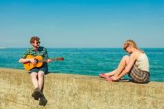 Jeune homme jouant la guitare à son amie extérieure Images libres de droits