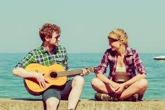 Jeune homme jouant la guitare à son amie extérieure Images stock
