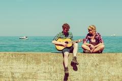 Jeune homme jouant la guitare à son amie extérieure Photographie stock libre de droits