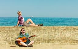 Jeune homme jouant la guitare à son amie par le bord de la mer Images stock