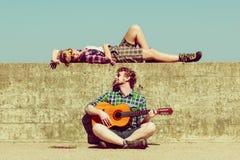 Jeune homme jouant la guitare à son amie par le bord de la mer Photos libres de droits