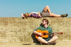 Jeune homme jouant la guitare à son amie par le bord de la mer Image stock