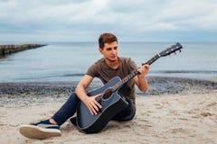 Jeune homme jouant la guitare acoustique se reposant sur le sable sur la plage dans Odesa photo libre de droits