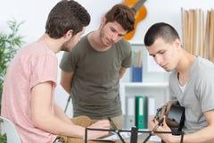 Jeune homme jouant la guitare avec des amis à la maison Photos libres de droits