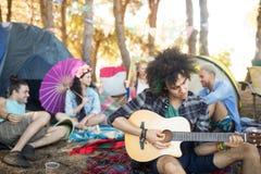 Jeune homme jouant la guitare avec des amis s'asseyant à l'arrière-plan Photos libres de droits