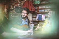 Jeune homme jouant la guitare en café à ses amis Photos libres de droits