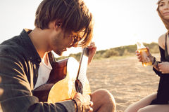 Jeune homme jouant la guitare pour des amis Photo stock