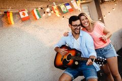 Jeune homme jouant la guitare pour les amis et son amie Images libres de droits