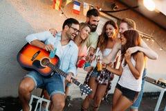 Jeune homme jouant la guitare pour les amis et son amie Photographie stock