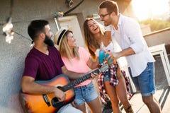 Jeune homme jouant la guitare pour les amis et son amie Photo stock