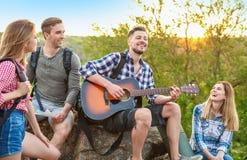 Jeune homme jouant la guitare pour ses amis dans la région sauvage Saison de camping Images stock