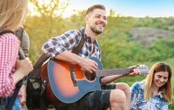 Jeune homme jouant la guitare pour ses amis dans la région sauvage Saison de camping Photographie stock libre de droits