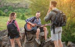 Jeune homme jouant la guitare pour ses amis dans la région sauvage Saison de camping Photos libres de droits
