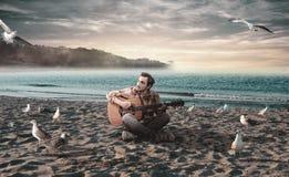 Jeune homme jouant la guitare sur la plage Image libre de droits