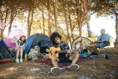 Jeune homme jouant la guitare tandis qu'amis s'asseyant au terrain de camping Image libre de droits