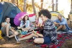 Jeune homme jouant la guitare tout en se reposant avec des amis au terrain de camping Photographie stock