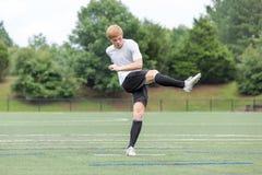 Jeune homme jouant le football - coups de pied de la boule photographie stock libre de droits