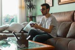 Jeune homme jouant le jeu vidéo tenant le contrôleur sans fil images stock