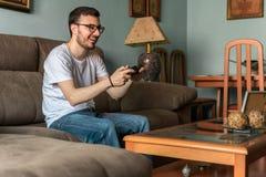 Jeune homme jouant le jeu vidéo tenant le contrôleur sans fil image libre de droits