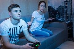 Jeune homme jouant un jeu vidéo à la maison et observé par son frustr Photos stock