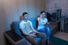 Jeune homme jouant un jeu vidéo tandis que son ressac d'amie dans Photos stock