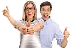 Jeune homme joyeux et femme tenant leurs pouces  images stock