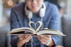 Jeune homme jugeant le livre avec la page de forme de coeur plié Images stock