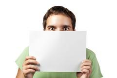Jeune homme jugeant un panneau-réclame blanc d'isolement Image stock