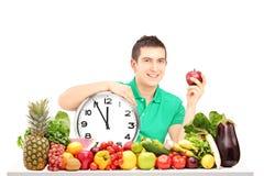 Jeune homme jugeant une horloge murale et une pomme, se reposant sur un ful de table Photos libres de droits