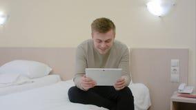 Jeune homme juste venant à une chambre d'hôtel, s'asseyant sur le lit et ayant la causerie visuelle sur le comprimé Photo libre de droits