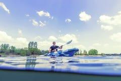 Jeune homme Kayaking sur le lac, vue sous-marine Kayaking, tir fendu photo libre de droits
