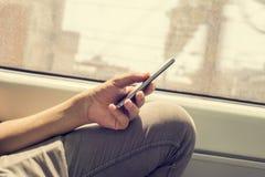 Jeune homme à l'aide d'un smartphone dans un train ou un souterrain Photo stock