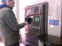 Jeune homme à l'aide du distributeur automatique inverse Image libre de droits