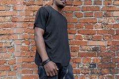 Jeune homme ? la peau fonc?e attirant dans le T-shirt noir sur le fond bricked rouge photographie stock
