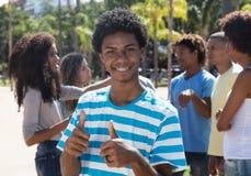 Jeune homme latino-américain avec des accolades montrant le pouce  Image libre de droits