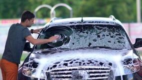 Jeune homme lavant le pare-brise sur sa voiture banque de vidéos