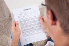 Jeune homme lisant un document de contrat Image stock