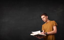 Jeune homme lisant un livre Photos libres de droits