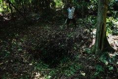jeune homme local de villageois avec un grand trou sur l'au sol de forêt tropicale de jungle censément un pas d'un géant image stock