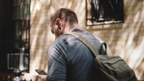 Jeune homme local heureux avec le sac à dos marchant lentement le long de la rue louche de ville d'été avec du café utilisant le  clips vidéos
