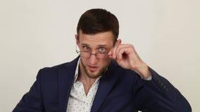 Jeune homme méfiant d'affaires avec des verres clips vidéos