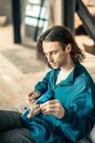 Jeune homme mélancolique dans le pull molletonné bleu installant son instrument de musique image stock