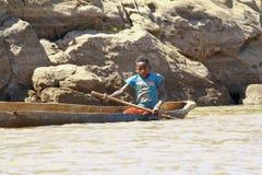 Jeune homme malgache de comble ramant le canoë traditionnel photo stock