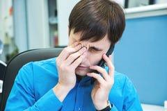 Jeune homme malheureux dans la dépression parlant du téléphone et ayant la mauvaise nouvelle image stock