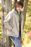 Jeune homme marchant à l'extérieur dans la régfion boisée d'automne photo libre de droits