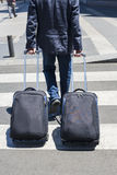 Jeune homme marchant avec deux valises Photographie stock