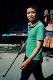 jeune homme marchant avec une arme à feu au marché photo stock